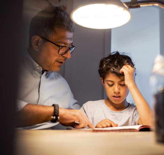 Father and son doing homework under a lamp